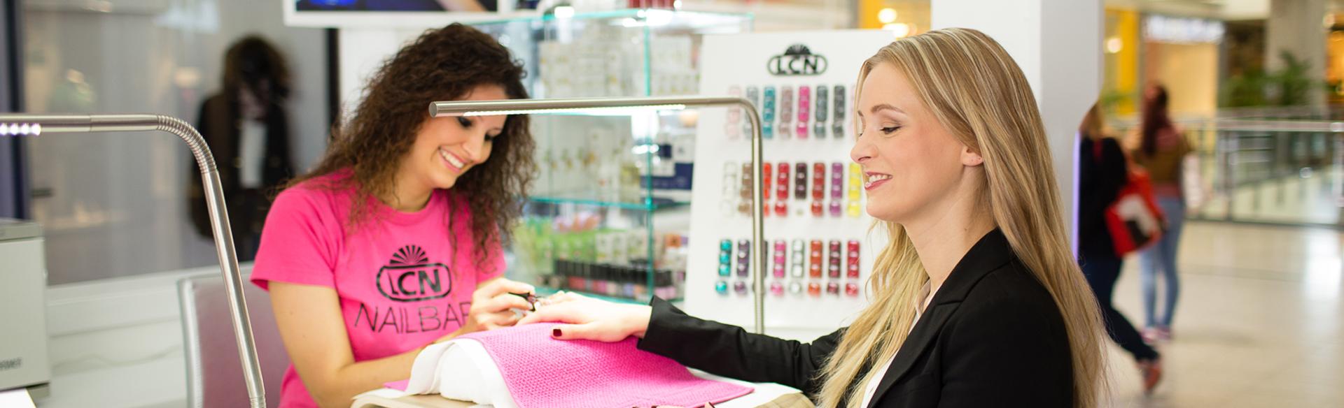 Клиентка у мастера маникюра сушит ногти в лампе