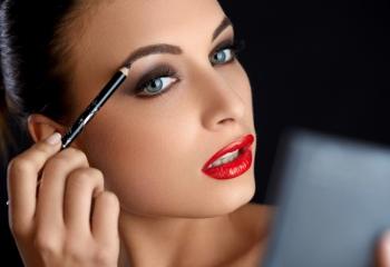 Модель рисует брови черным карандашом
