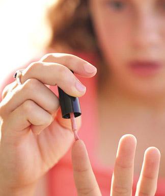 Девушка сама себе наносит гель-лак на ногти